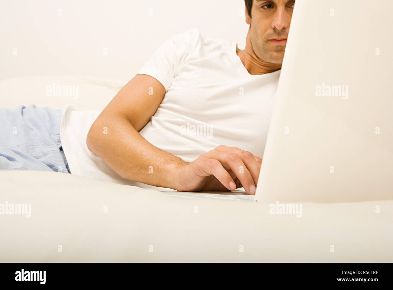 Man on bed using laptop computer - Stock Image
