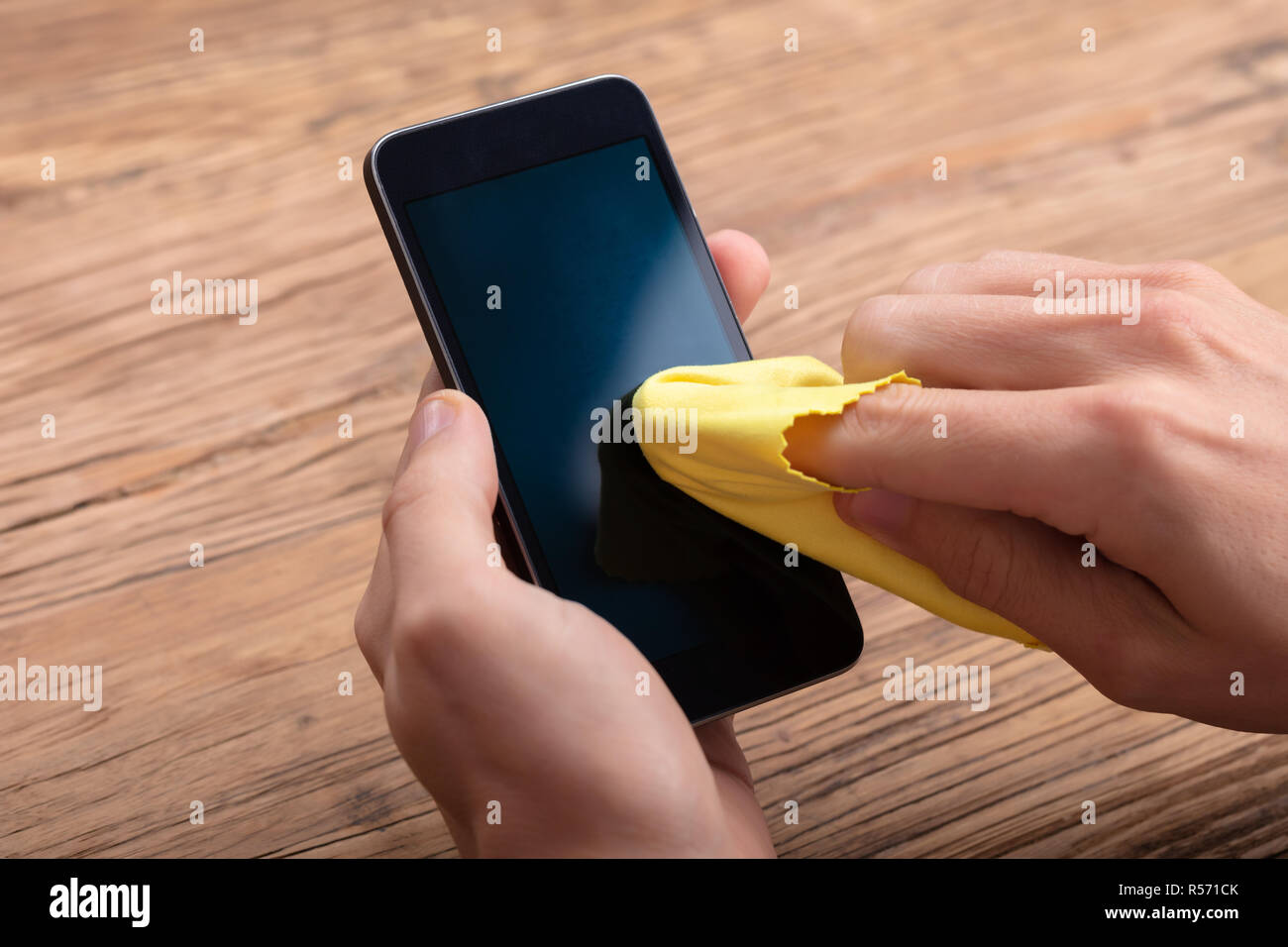 Man Cleaning Mobile Phone Screen With Yellow Cloth Over Wooden Desk Stock Photo