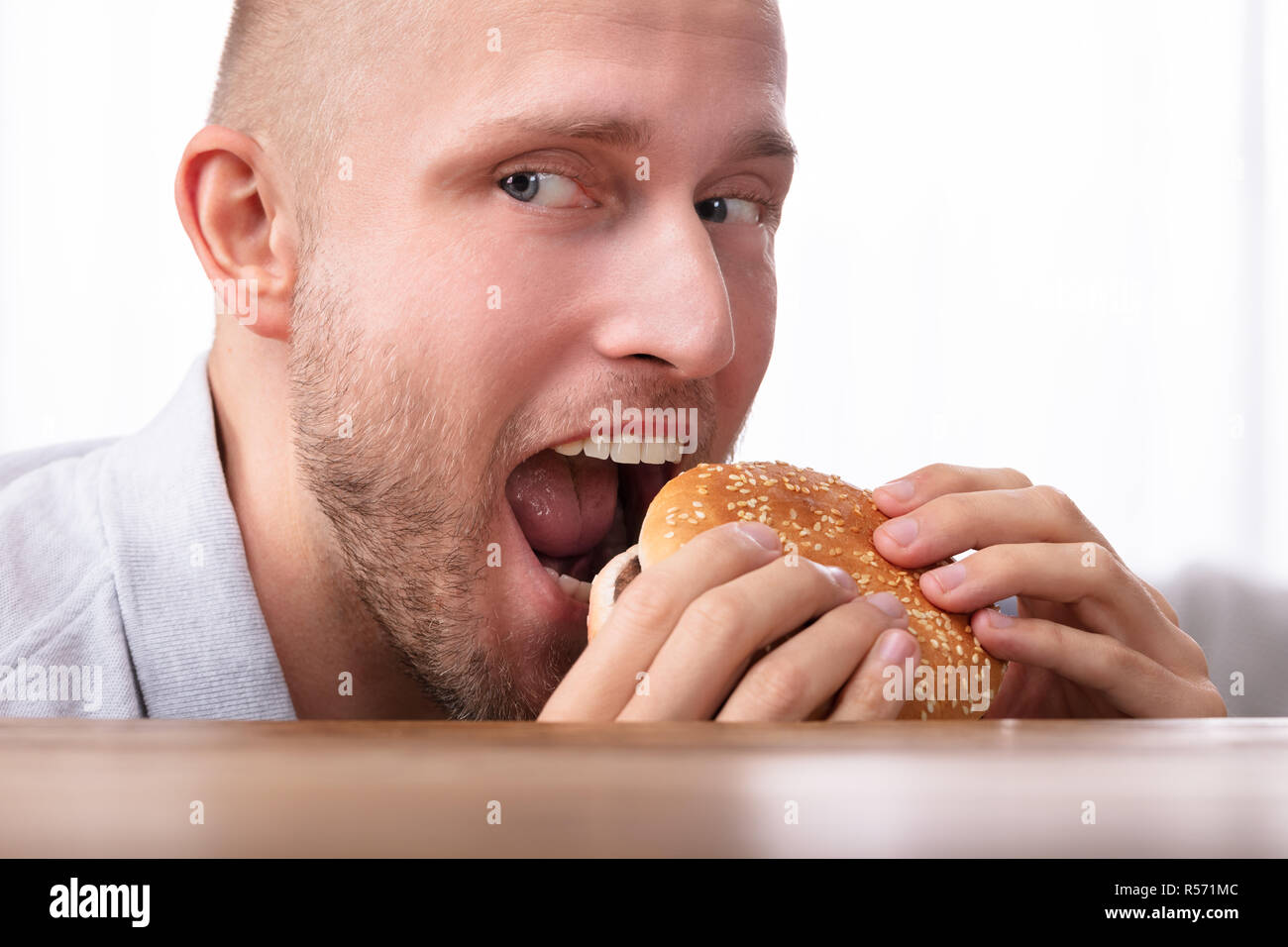 Portrait Of A Greedy Young Man Eating Burger - Stock Image
