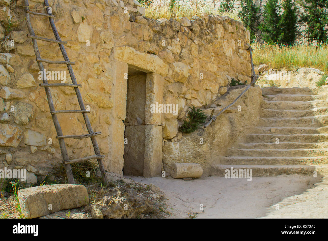 A retro style stone house in the open air museum of Nazareth Village Israel. houses in the modern Nazareth can be seen in the background. This site gi Stock Photo