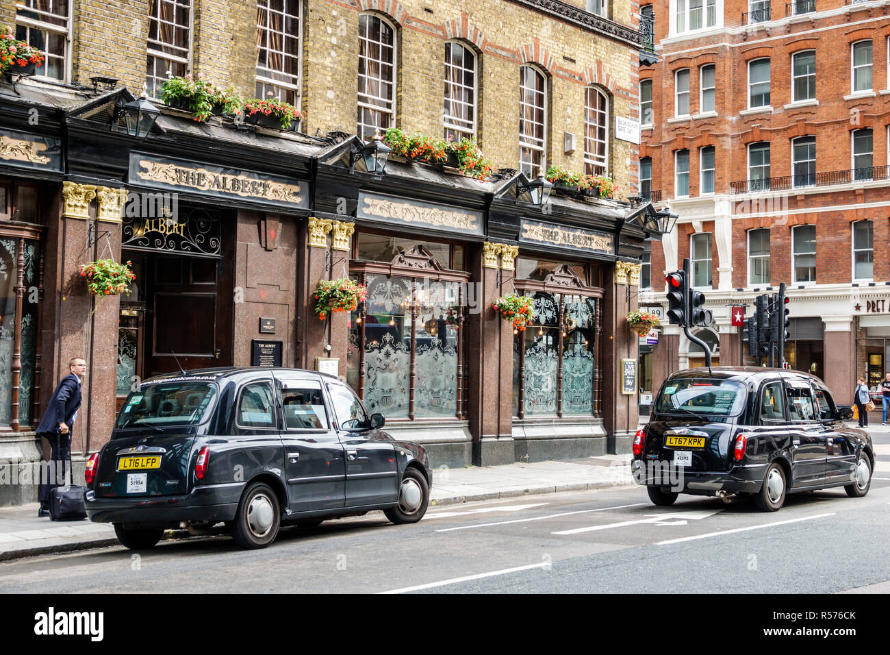 London England United Kingdom Great Britain Westminster Victoria Street The Albert Pub Victorian public house building exterior black taxicab taxi hac Stock Photo