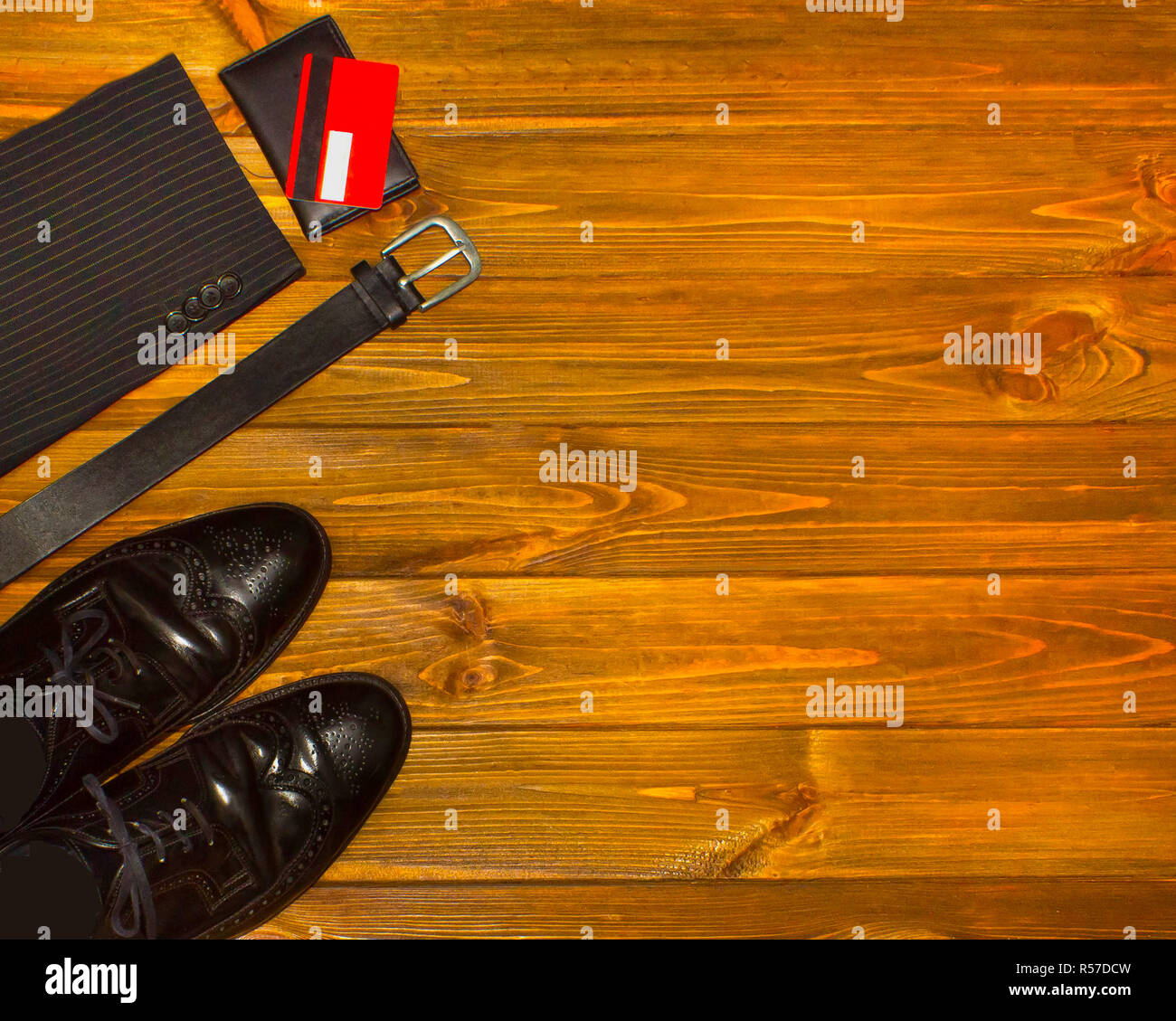 The elegant male set: men's shoes, leather belt, on the wooden background. Stock Photo