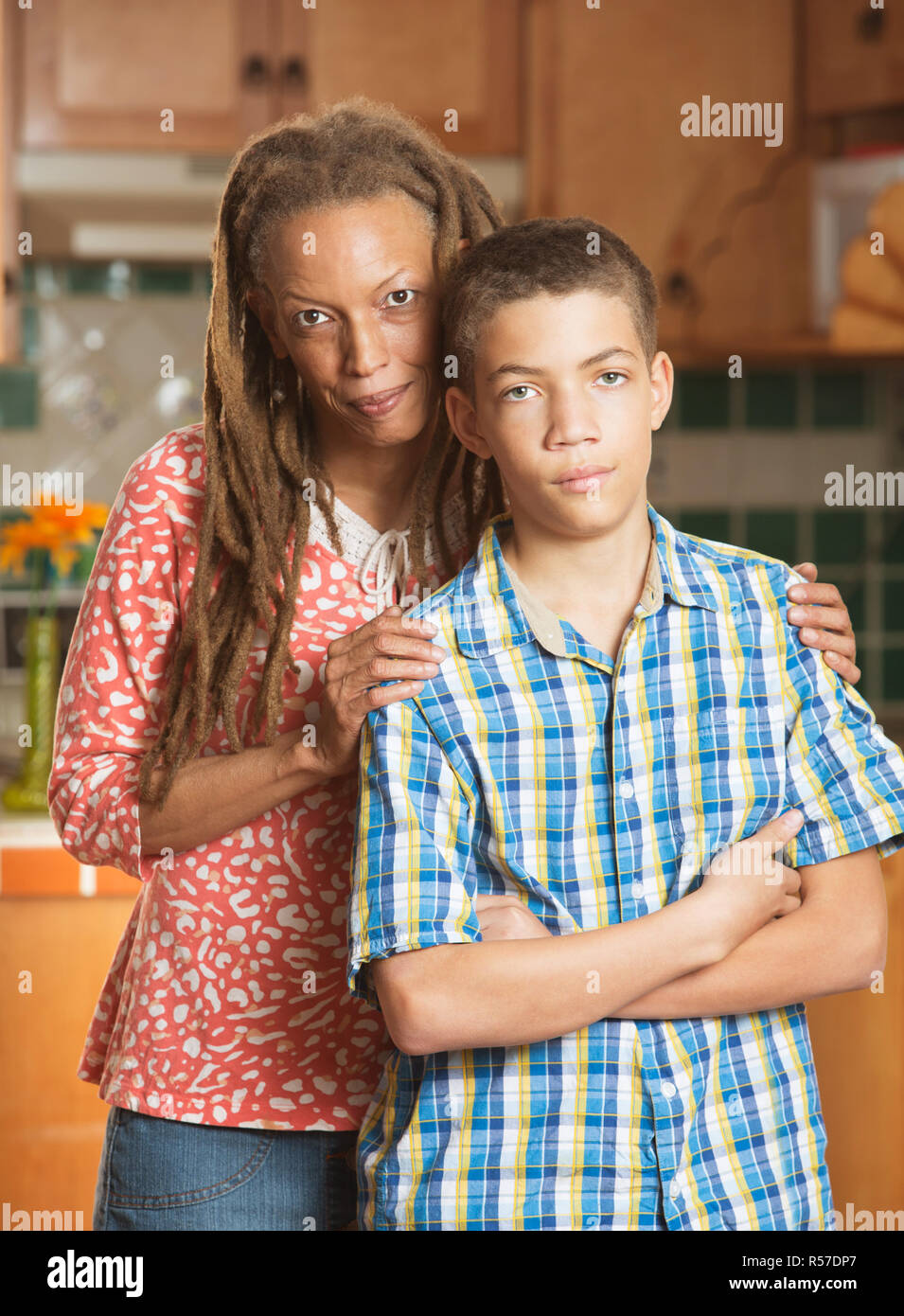 Disagreeable teen boy stands grimacing beside his loving mother - Stock Image