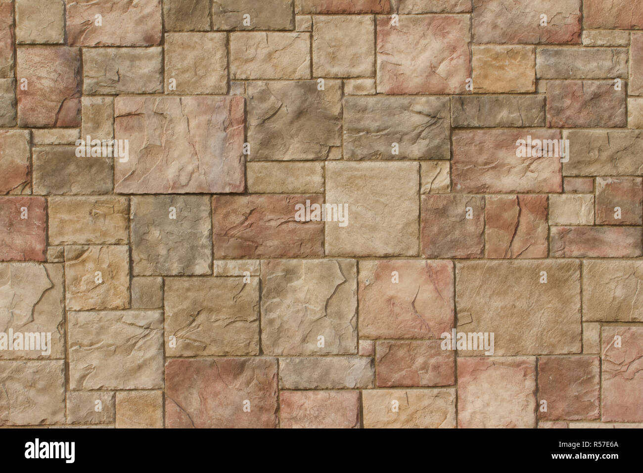 Textured marble look stone brick wall background in shades of beige, red and light brown - Stock Image