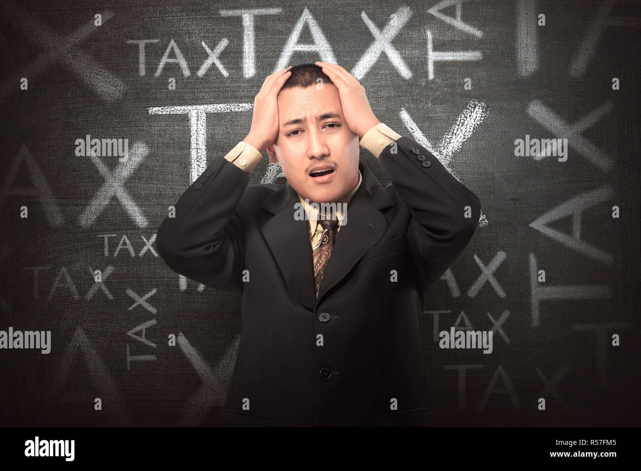 Stressful businessman with Tax text sign - Stock Image