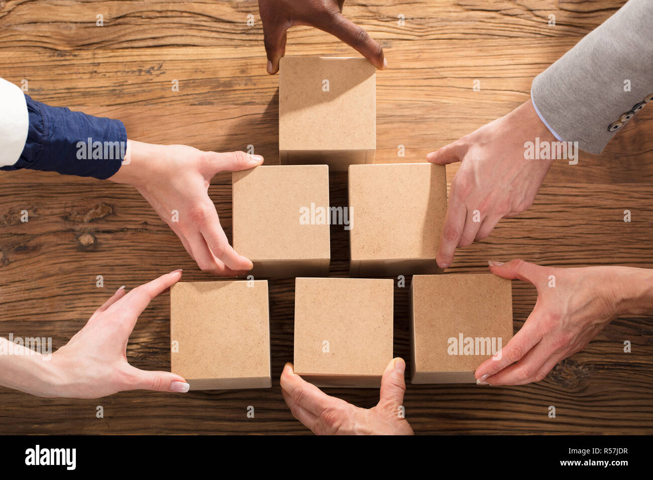 People Arranging Block On Pyramid Stock Photo