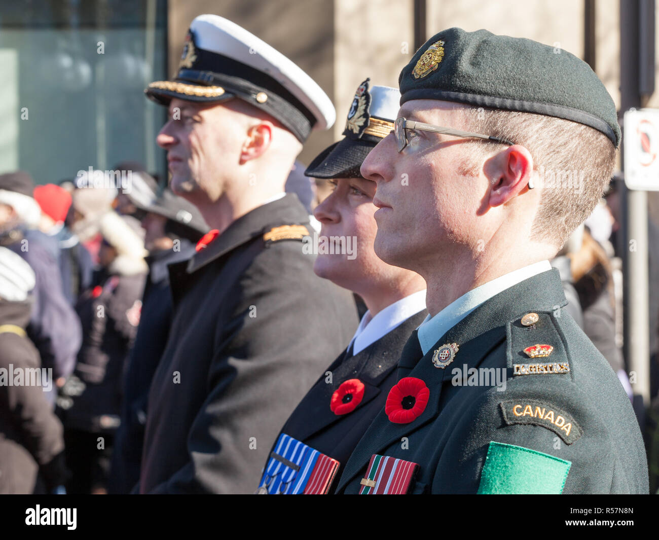 OTTAWA, CANADA - NOVEMBER 11, 2018: Soldiers from Canadian Army, two men, a woman, from Navy & ground forces, wearing remembrance poppy, standing on c - Stock Image