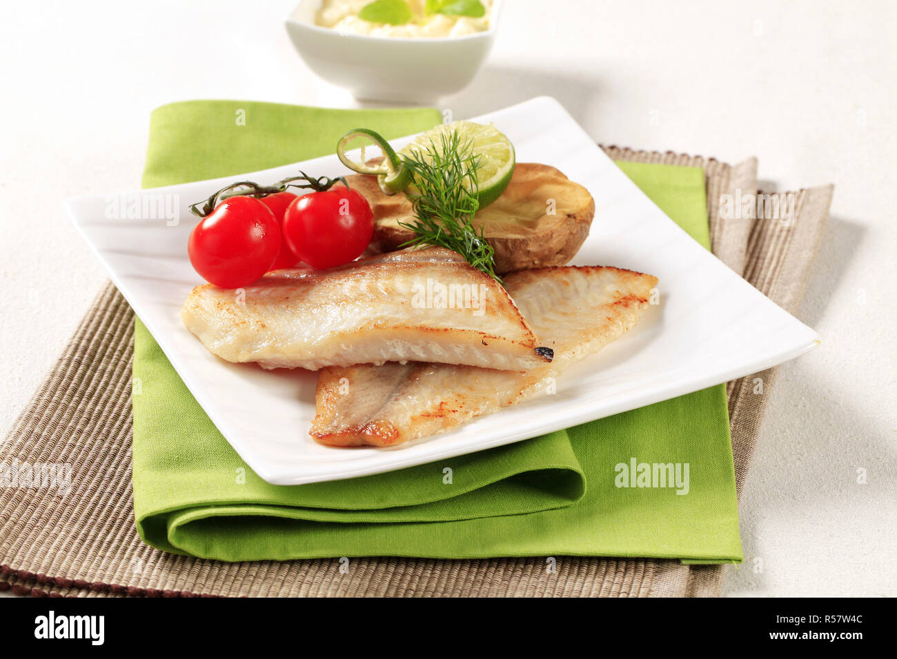 Skinless fish fillets with baked potato half - Stock Image
