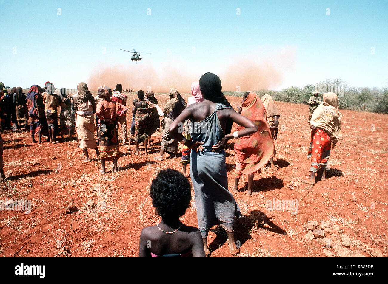 1993 - Villagers watch as a Marine Heavy Helicopter Squadron 363 (HMH-363) CH-53D Sea Stallion helicopter lifts off after delivering a load of grain during the multinational relief effort OPERATION RESTORE HOPE. Stock Photo