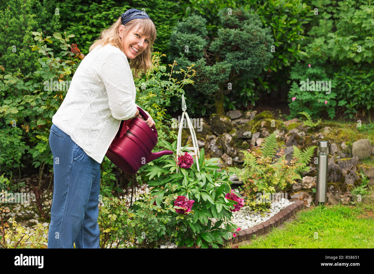 friendly woman is pouring peonies in the garden - Stock Image