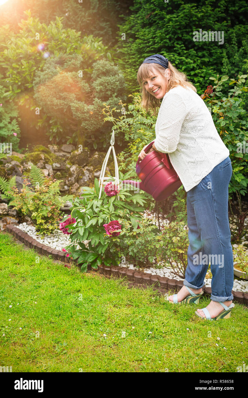 nice woman pours peonies in the garden - Stock Image