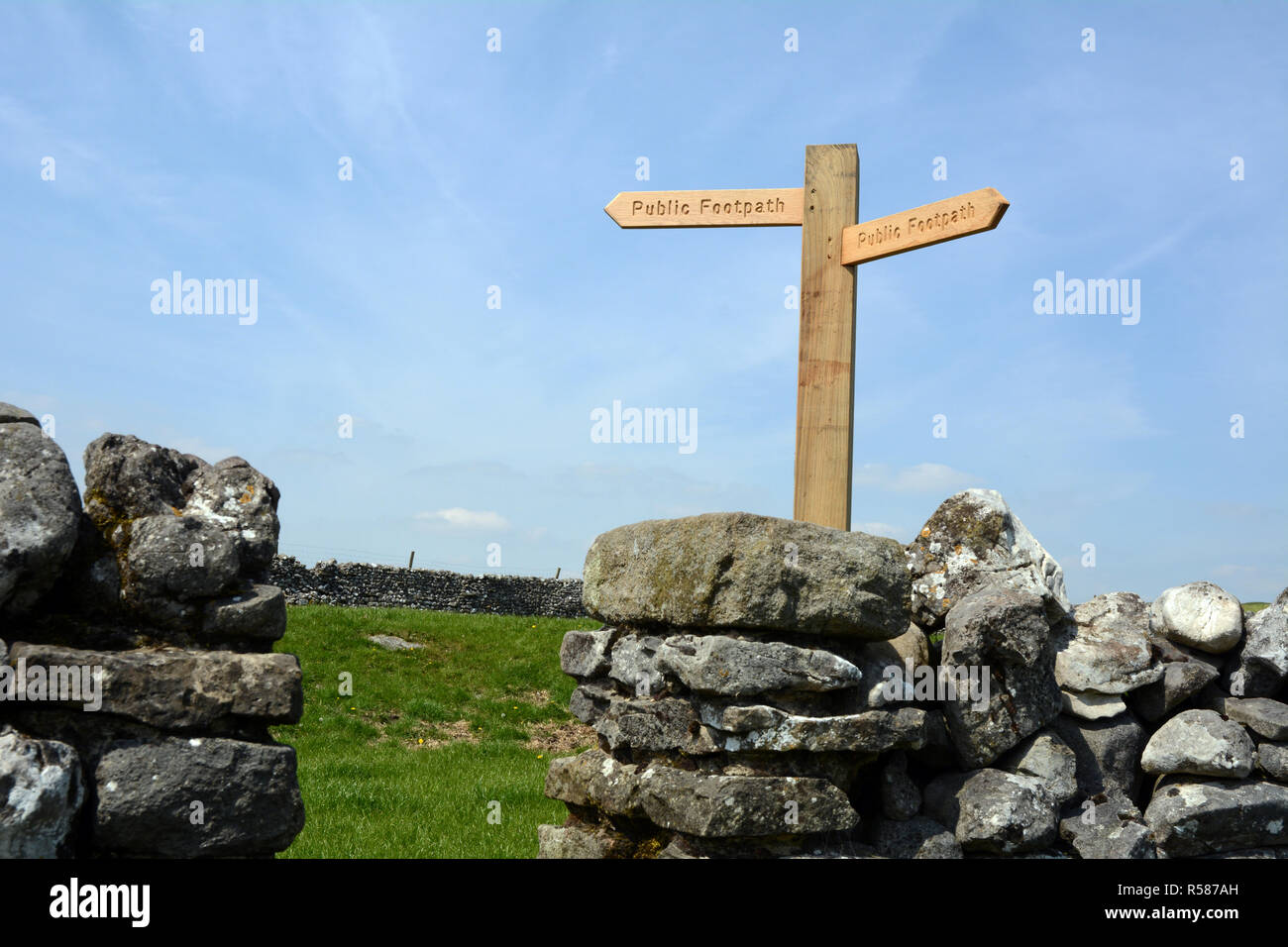 A sign atop a dry stone wall reading 'public footpath' indicating the direction of The Dales Way hiking trail in Yorkshire, England, United Kingdom - Stock Image