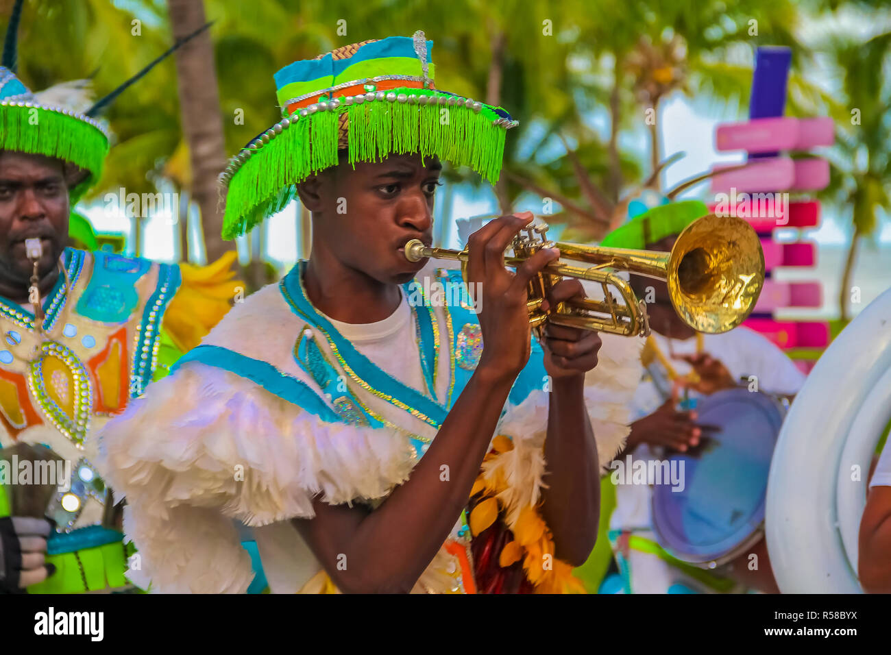 Freeport Bahamas - September 22, 2011: Male dancers dressed in traditional costumes performing at a Junkanoo festival playing a trumpet in Freeport, B - Stock Image