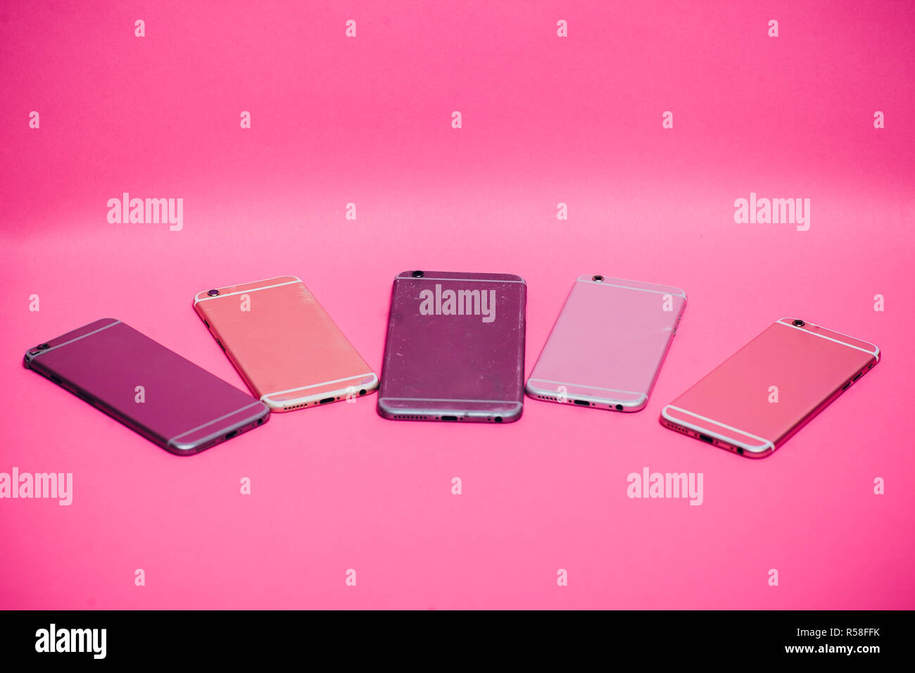 Broken mobile phone lies on a pink background. - Stock Image