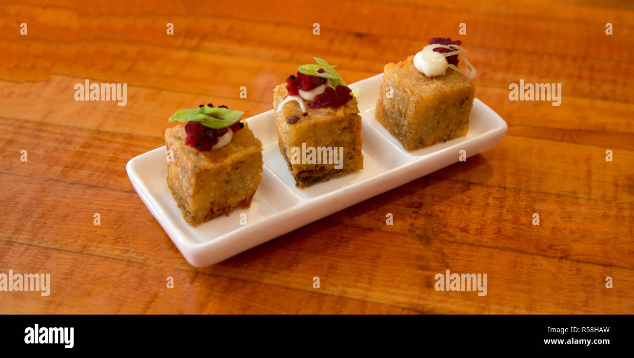 Appetizing tapas of tasty potato and ham bites with red beet relish and aioli in white, segmented dish on wood table top - Stock Image