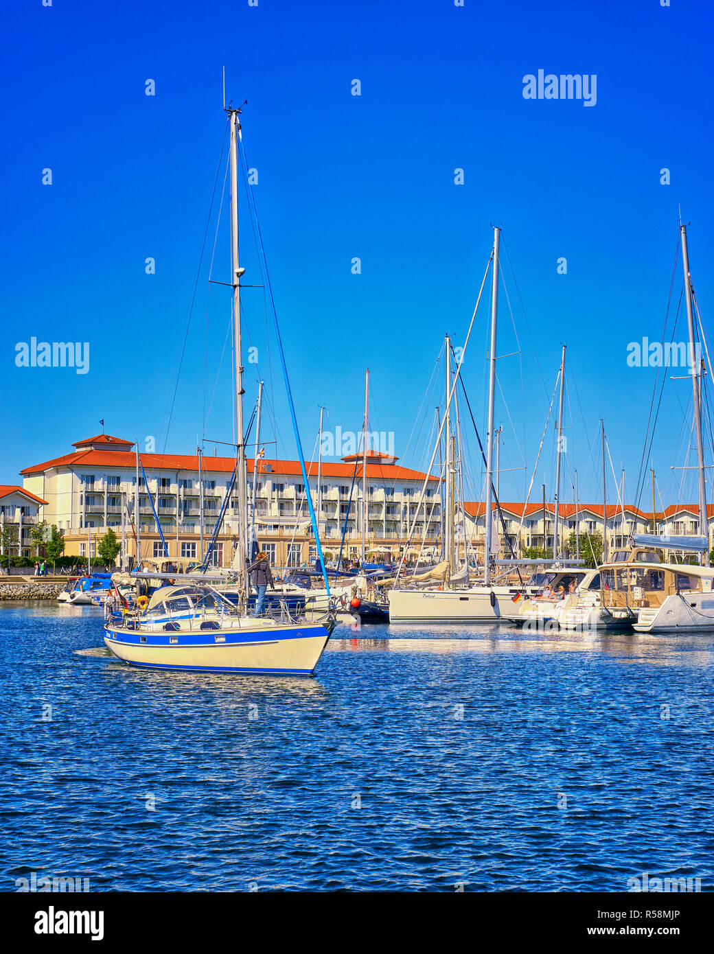 Holiday houses with sailboats in the harbor Weiße Wiek. - Stock Image