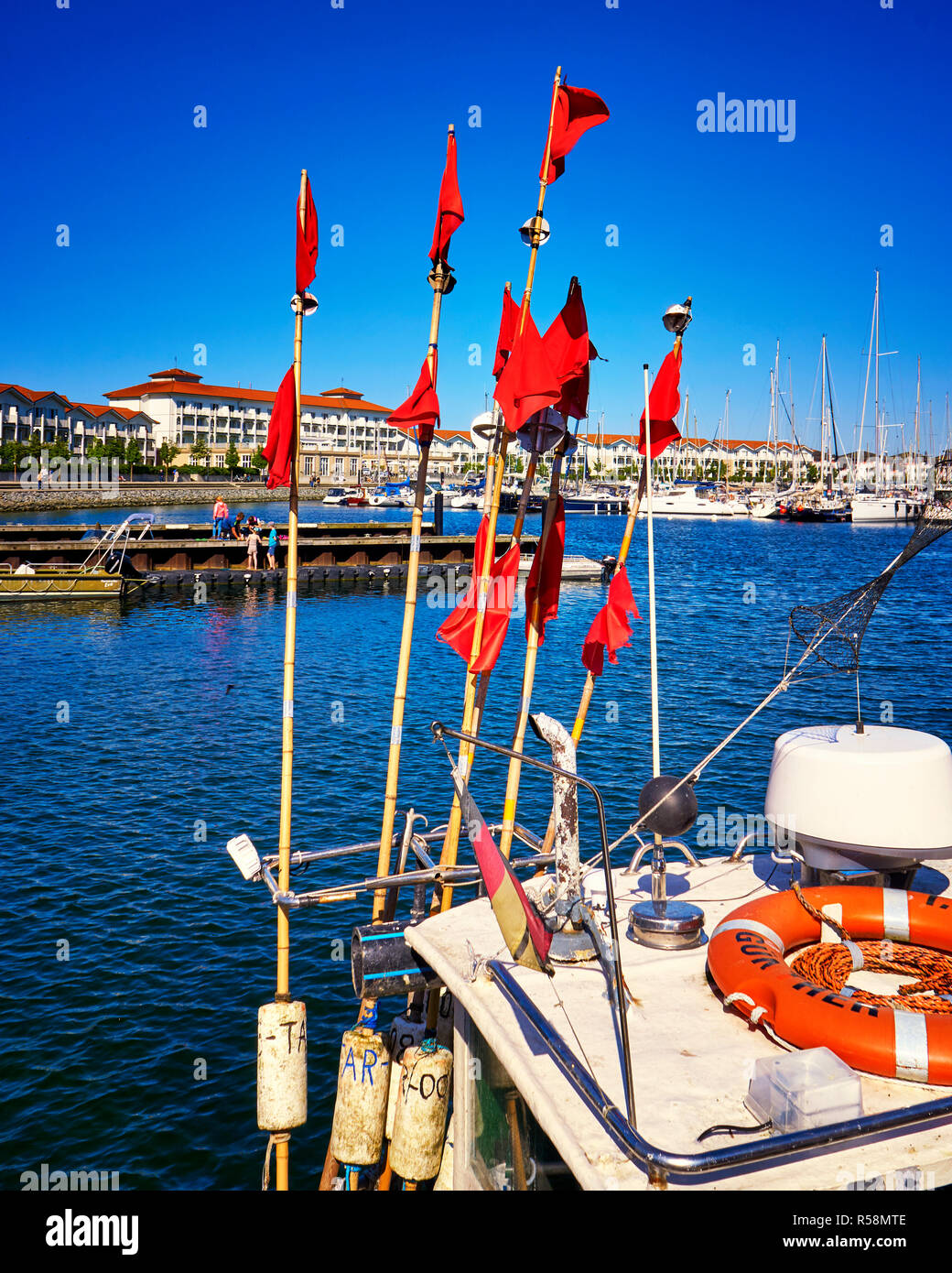 Red flags on the fishing boat in the harbor Weiße Wiek. - Stock Image