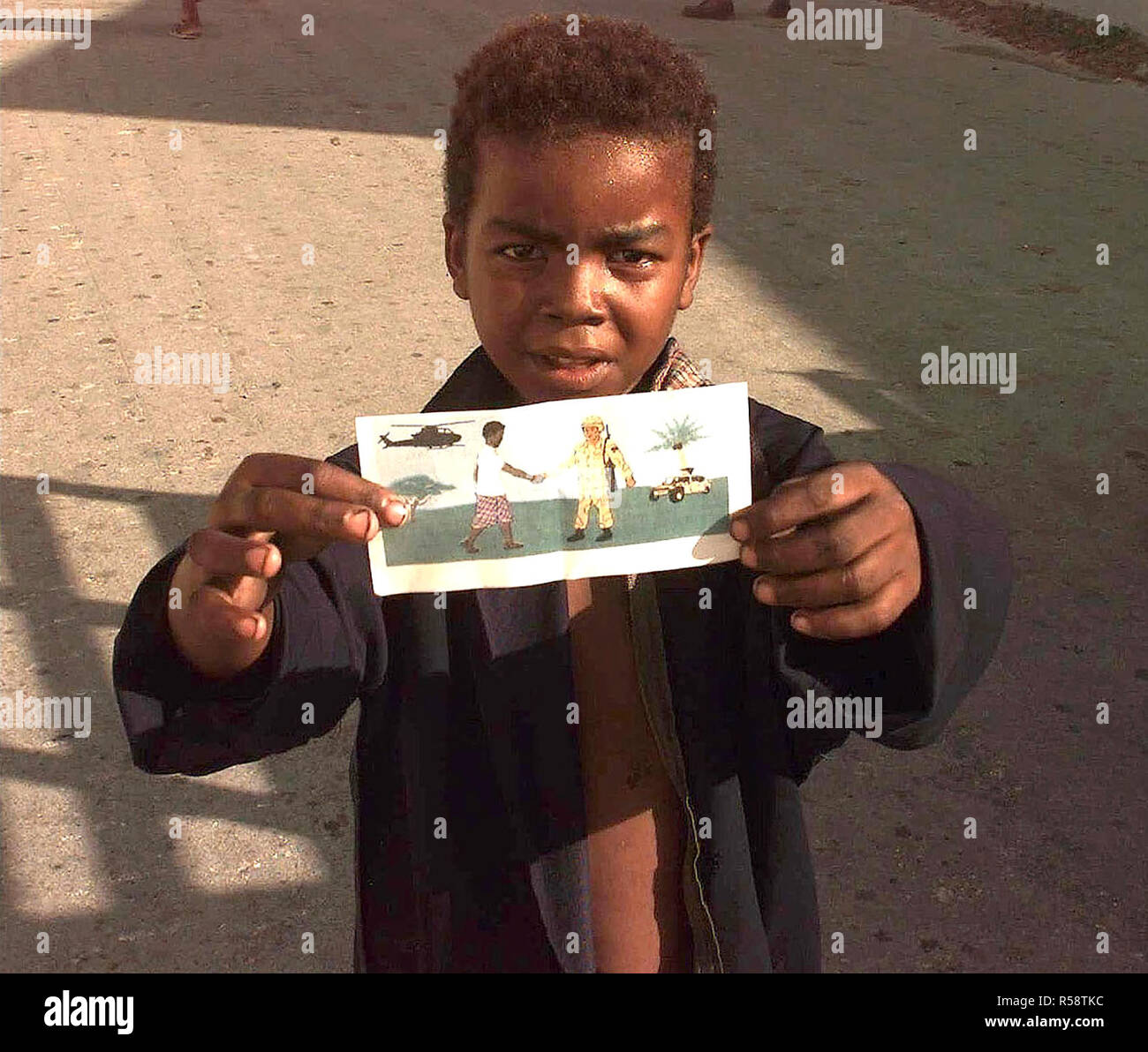 1993 - A young Somali boy holding one of the PSYOPS leaflets up to the camera.  The leaflet is a hand drawing a Somali man shaking the hand of a US Forces member.  The drawing conveys to the Somali people that the US is trying to help end their suffering and is here as their friends. - Stock Image