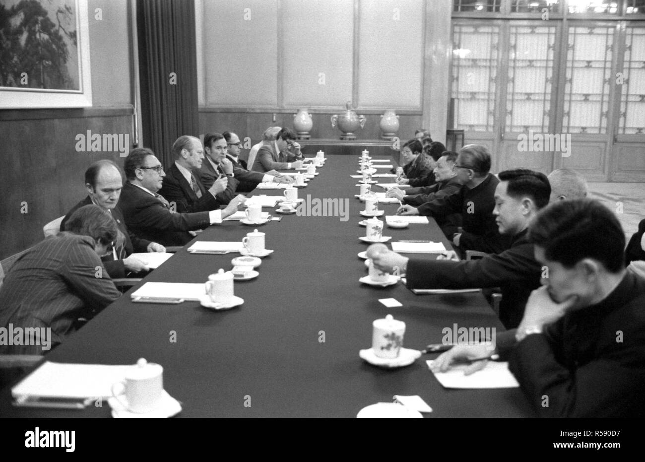 This photograph depicts President Ford, Secretary of State Henry Kissinger, Chief U.S. Liaison Officer George H. W. Bush and the President's staff as they hold bilateral talks with People's Republic of China (PRC) Vice-Premier Teng Hsiao-P'ing and other officials in the Great Hall of the People. - Stock Image