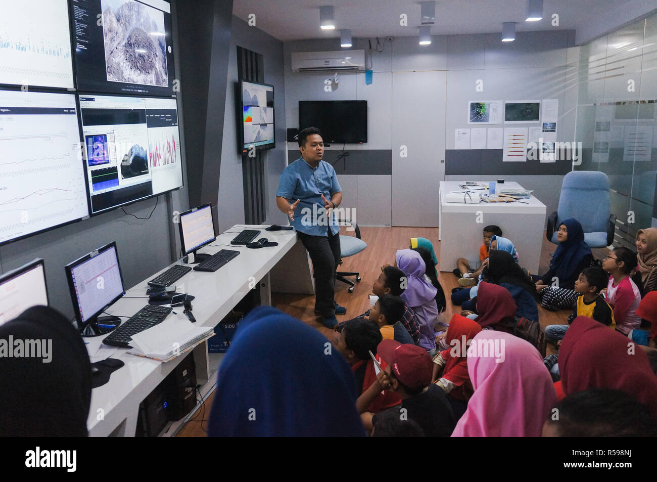 Yogyakarta, Indonesia. 30th Nov, 2018. A volcanologist was explaining the kids in Merapi mountain's observation room. This activity is a mitigation program for people that live under Merapi mountain. Credit: Galih Yoga Wicaksono/Alamy Live News - Stock Image