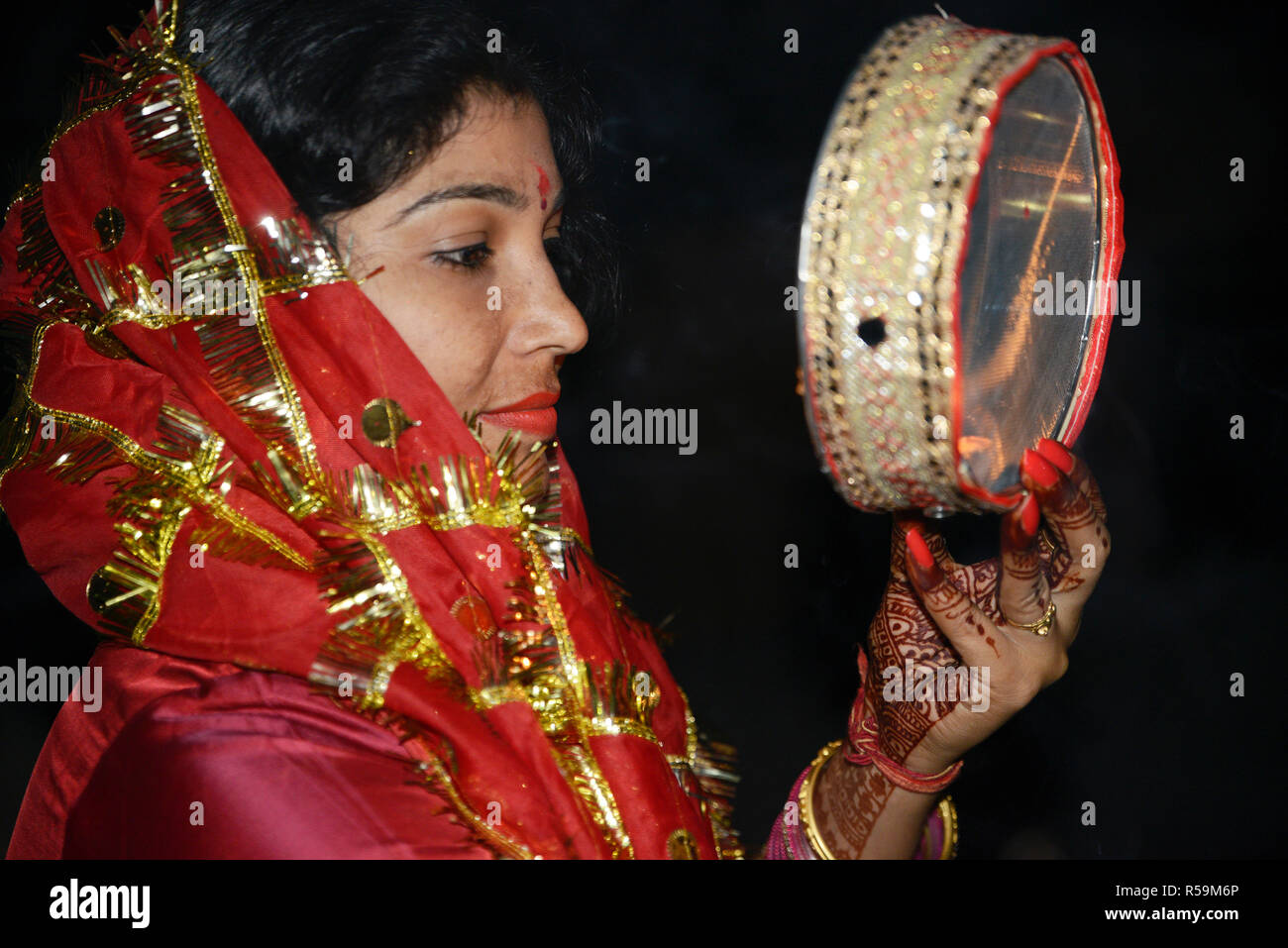 Woman Looking at moon through a sieve during Karva Chauth - Stock Image