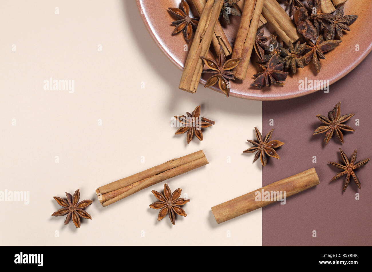 Cinnamon and anise stars in a plate and near on a two-tone background, top view with copy space - Stock Image