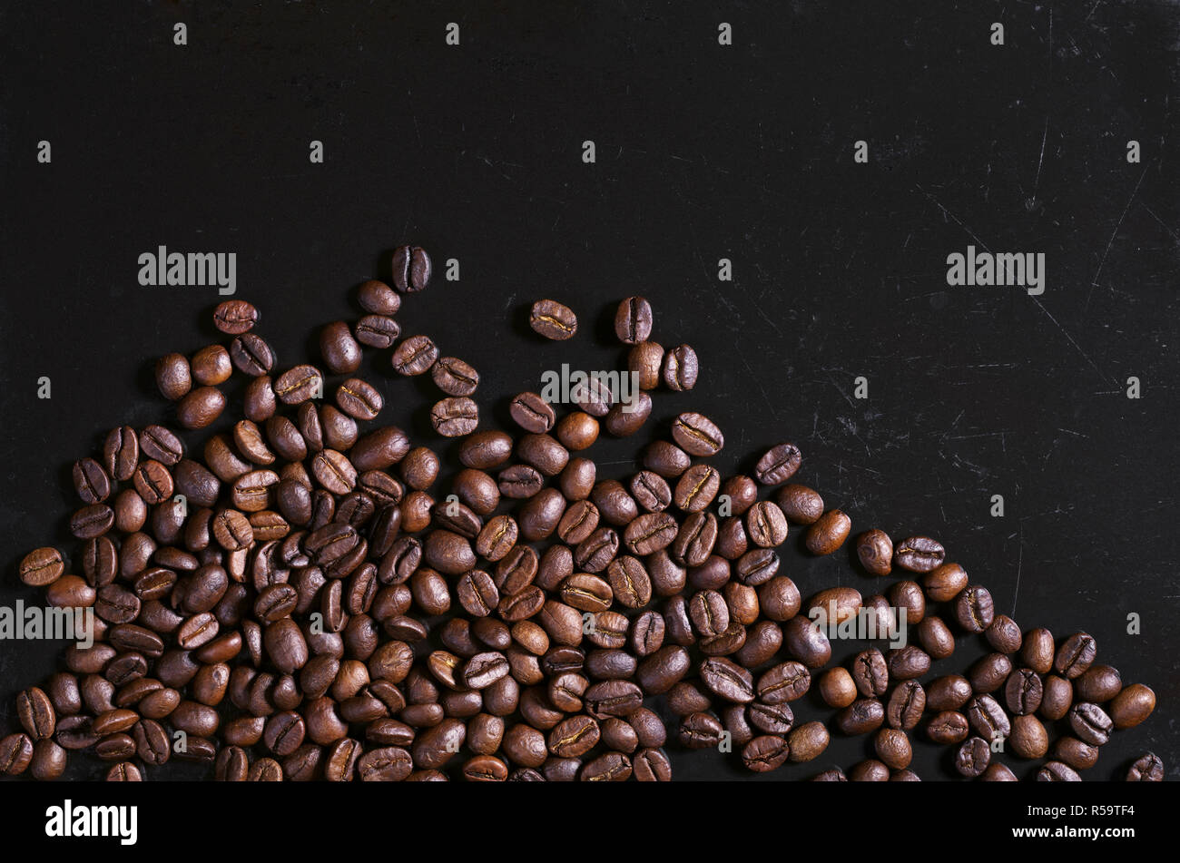 Coffee beans scattered on old black metal background space for your