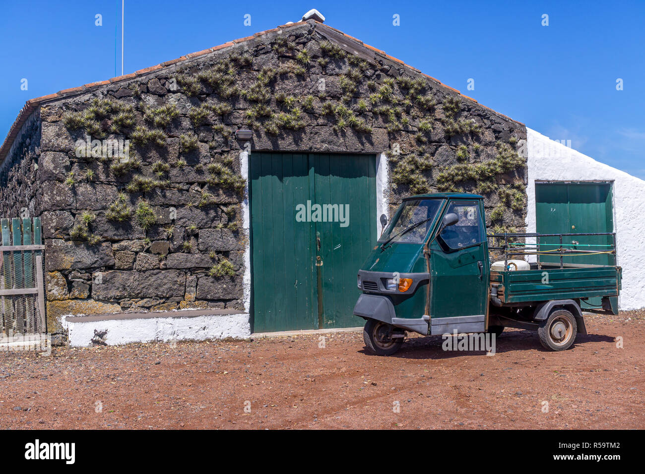 Building used for storing and making wine with a small, old utility vehicle parked in front. Pico Island, Azores, Portugal - Stock Image