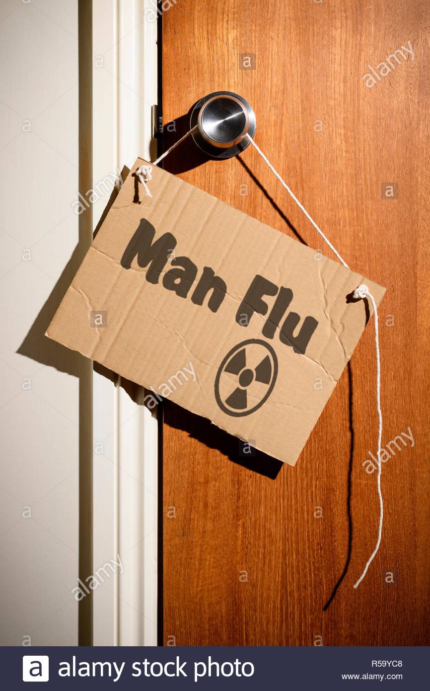 Man Flu written on a makeshift sign hanging on the door handle, Dorset, England. - Stock Image
