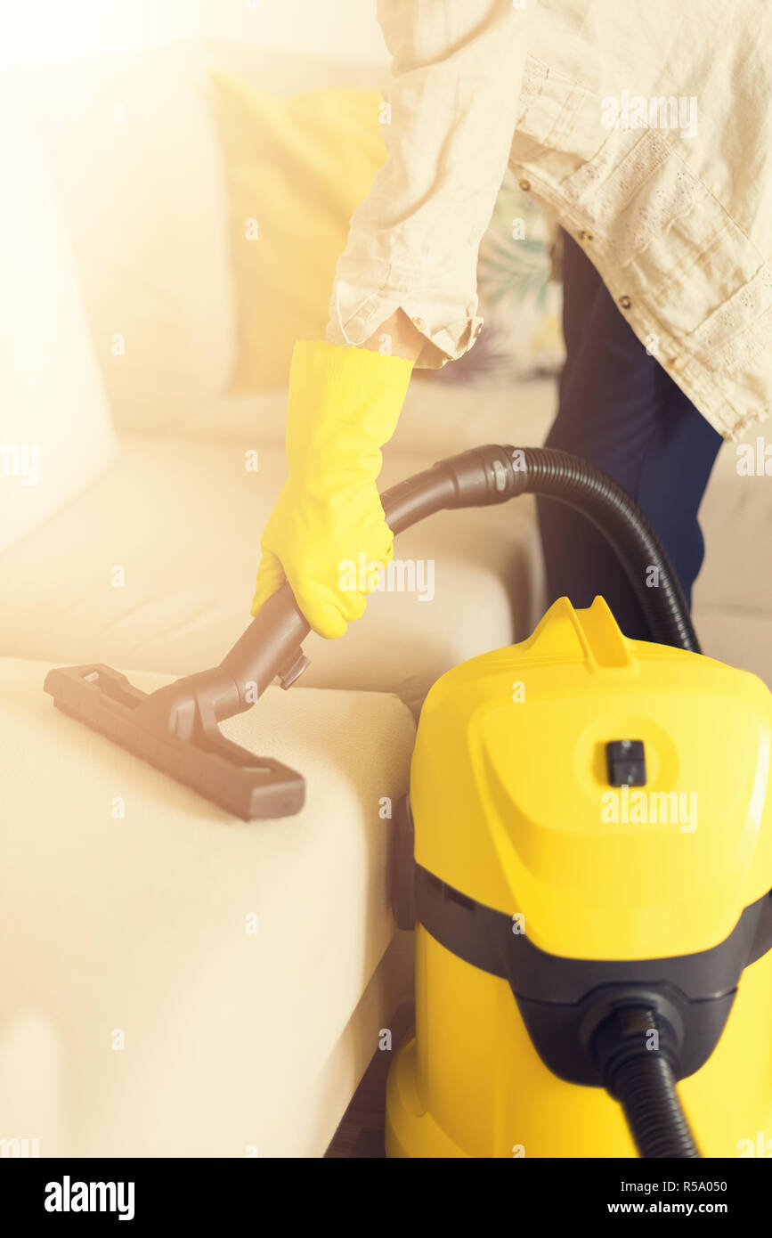 Woman cleaning sofa with yellow vacuum cleaner. Copy space. Clean concept. Stock Photo