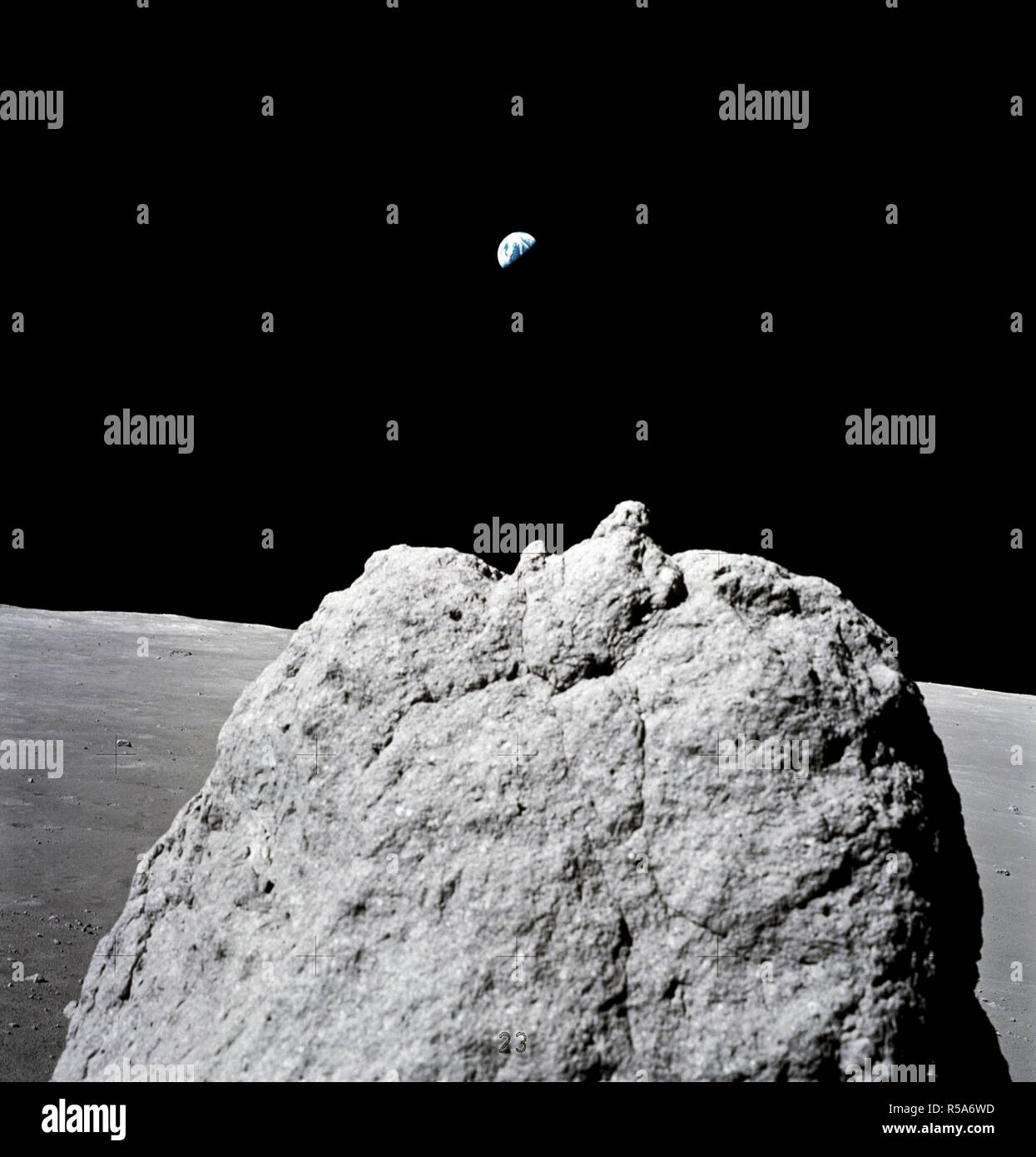 (7-19 Dec. 1972) --- Earth (far distant background) is seen above a large lunar boulder (foreground) on the moon. The photo was taken with a handheld Hasselblad camera by the last two moon walkers in the Apollo Program. - Stock Image