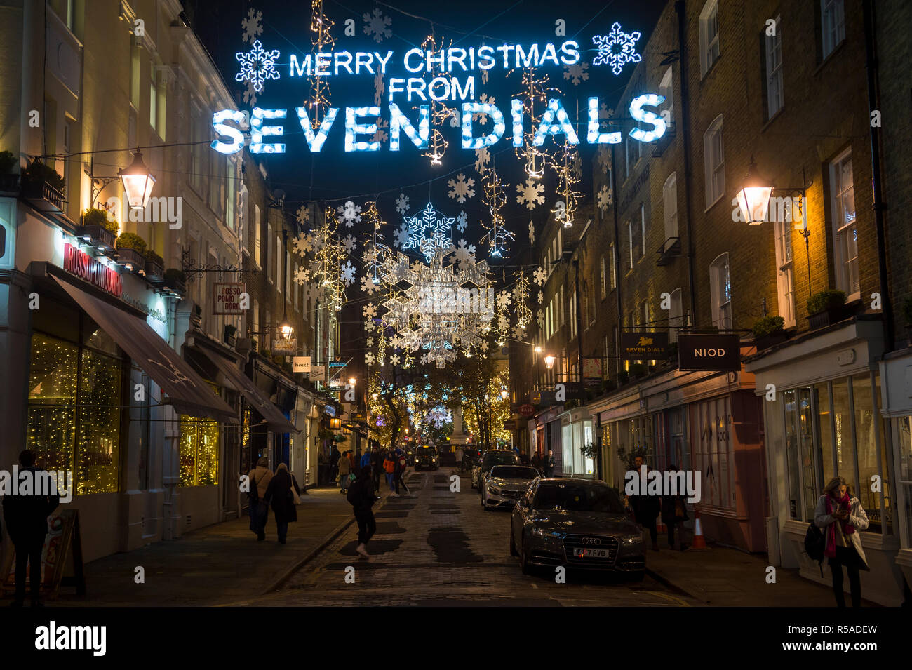 LONDON - NOVEMBER 26, 2018: Merry Christmas from Seven Dials message hangs with sparkling holiday lights in the popular West End neighbourhood. - Stock Image
