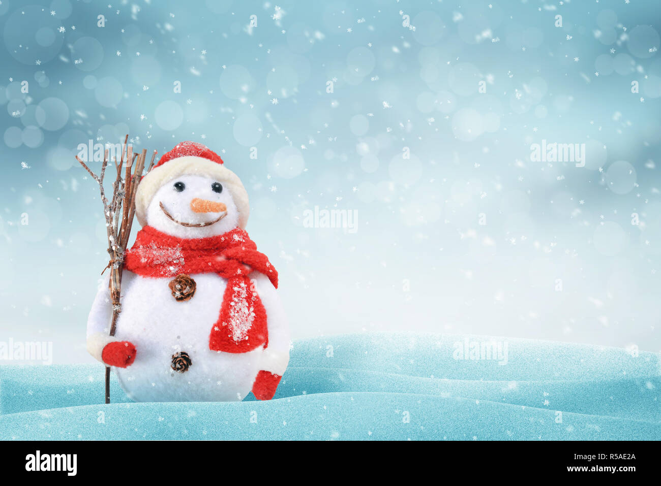 Christmas scene with a cute snowman. Free space for text on right side. snob, light and bokeh in background. - Stock Image