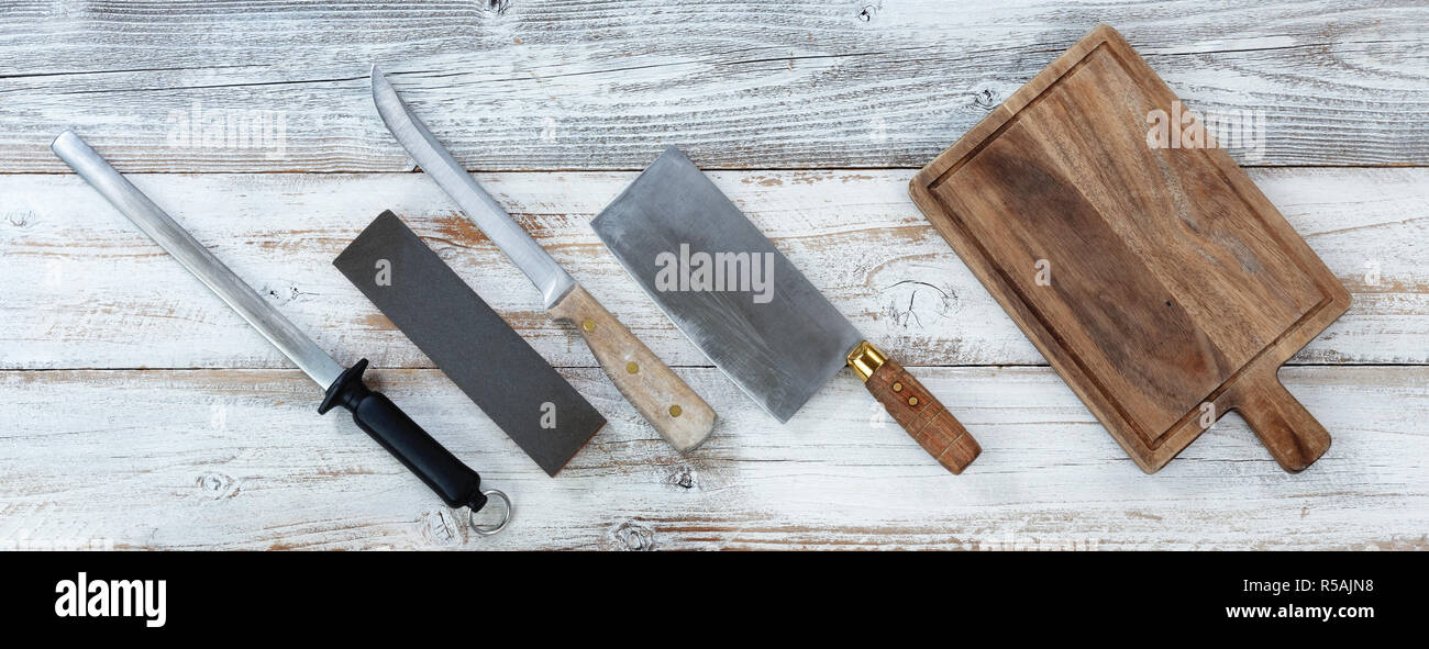 Cooking knives with wet stone and steel for sharpening on white rustic wooden boards - Stock Image