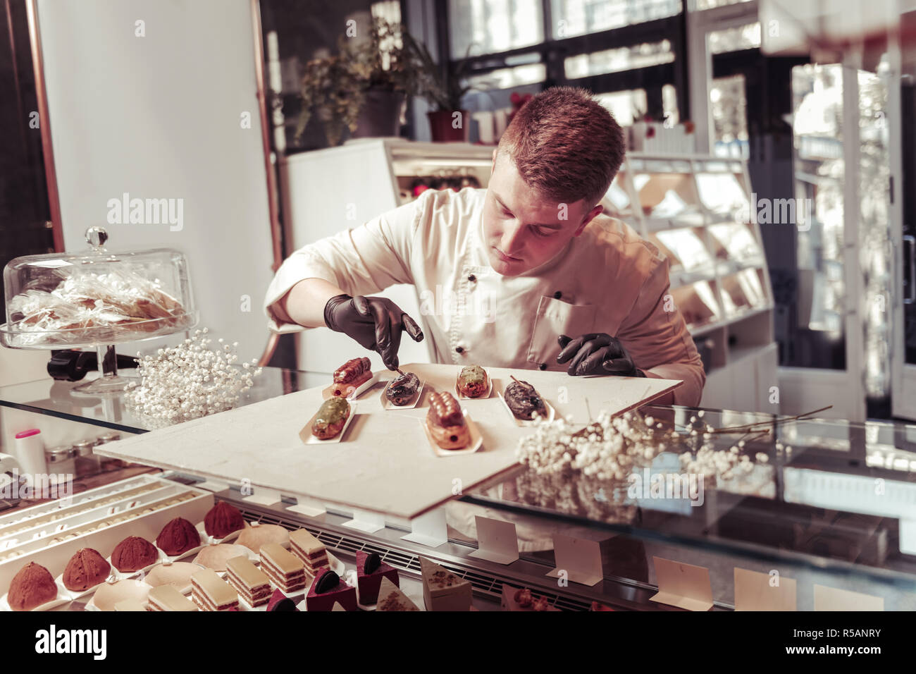 Sweet cakes. Nice professional confectioner looking at the tasty eclairs while decorating them - Stock Image