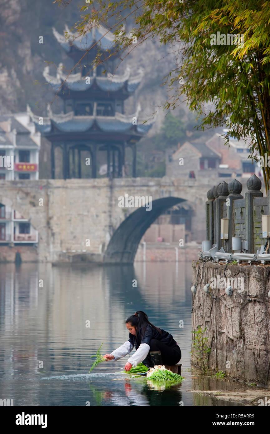 Woman washing vegetables in river, Zhenyuan, Guizhou, China Stock Photo