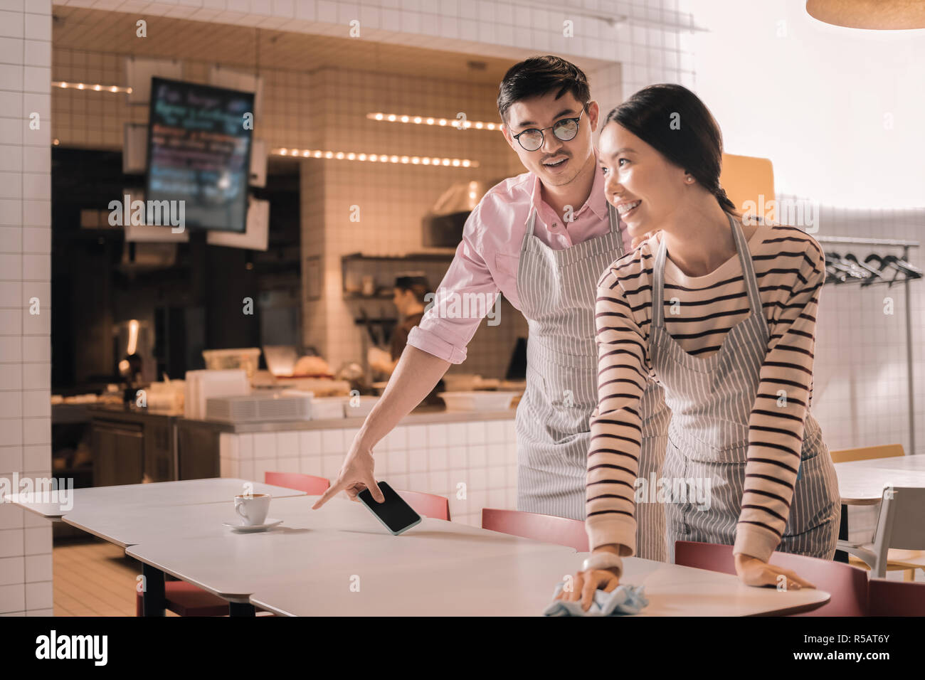 Young couple working part time job as waiters in the restaurant - Stock Image
