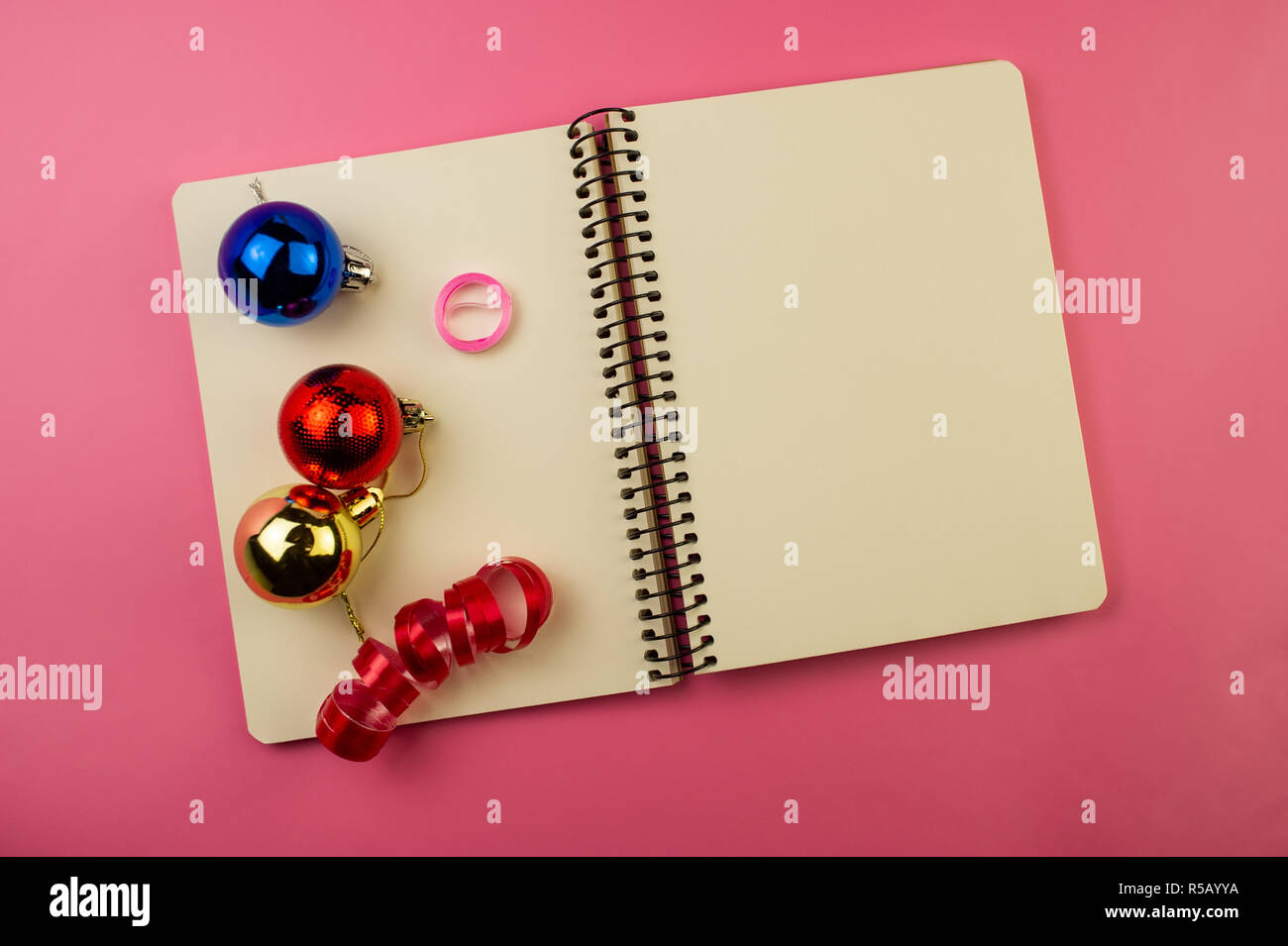 Open Notebook And Christmas Decorations On A Pink Background