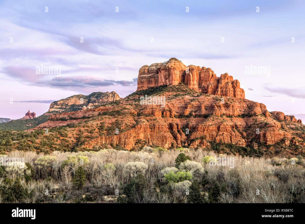 The setting sun paints the sky and rock formations of Sedona, Arizona including Cathedral Rock to the right. Stock Photo