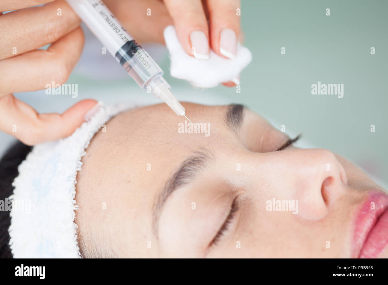 Doctor applying a facial treatment using a syringe Stock Photo