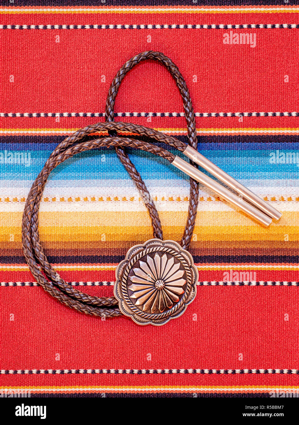 Vintage Sterling Silver Bolo Tie with Concho and Silver Tips on colorful southwestern hand woven fabric. - Stock Image