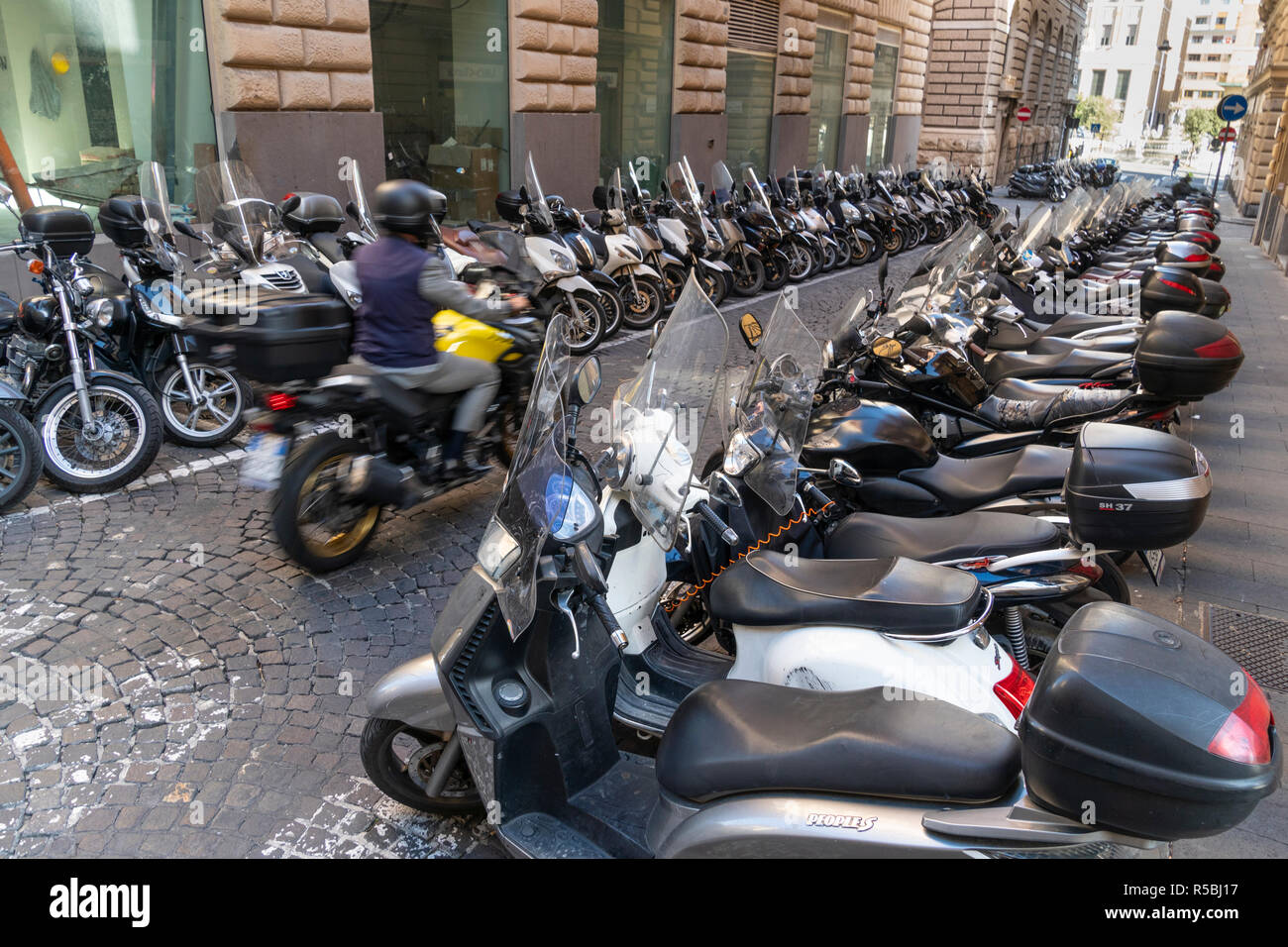 Rows of scooters and motorbikes, the most popular transport in Naples, parked in a street in the city centre,  Naples, Italy. - Stock Image