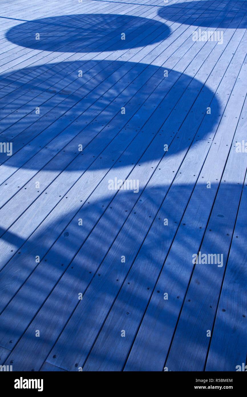 Israel, Tel Aviv, Old Port, Namal, renovated port now home to shops and cafes, umbrella shadows on boardwalk - Stock Image