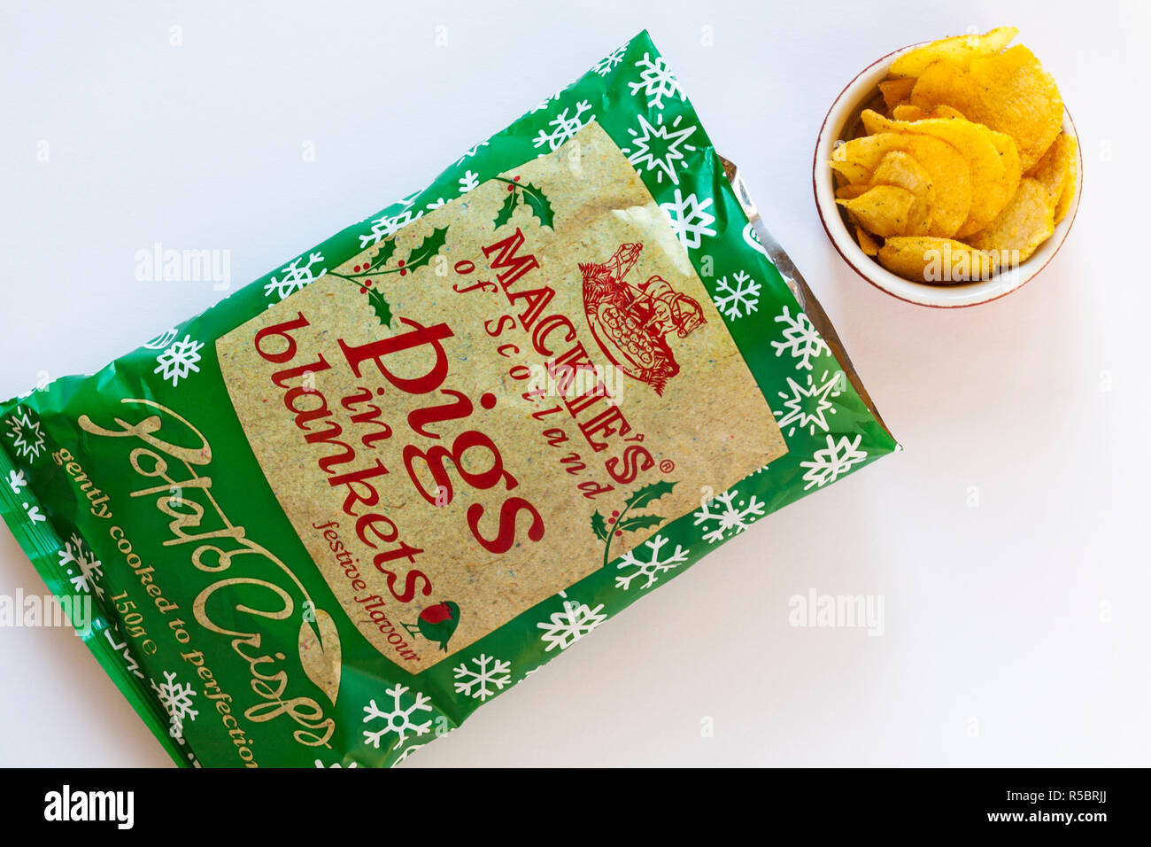 open packet of Mackie's of Scotland Pigs in Blankets festive flavour Potato Crisps with crisps in bowl set on white background - ready for Christmas - Stock Image