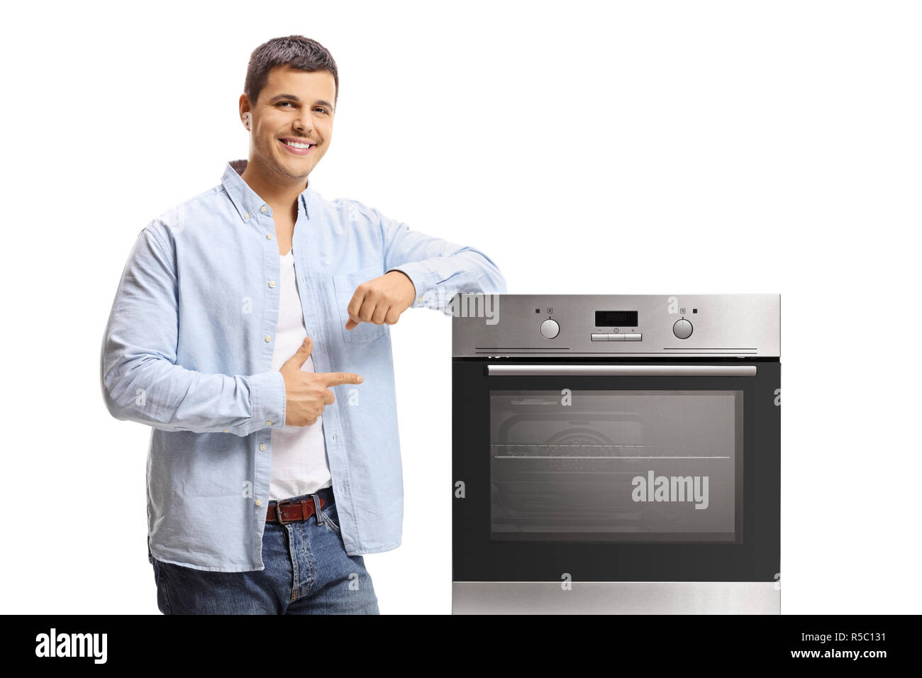 Young man leaning on an oven and pointing isolated on white background - Stock Image