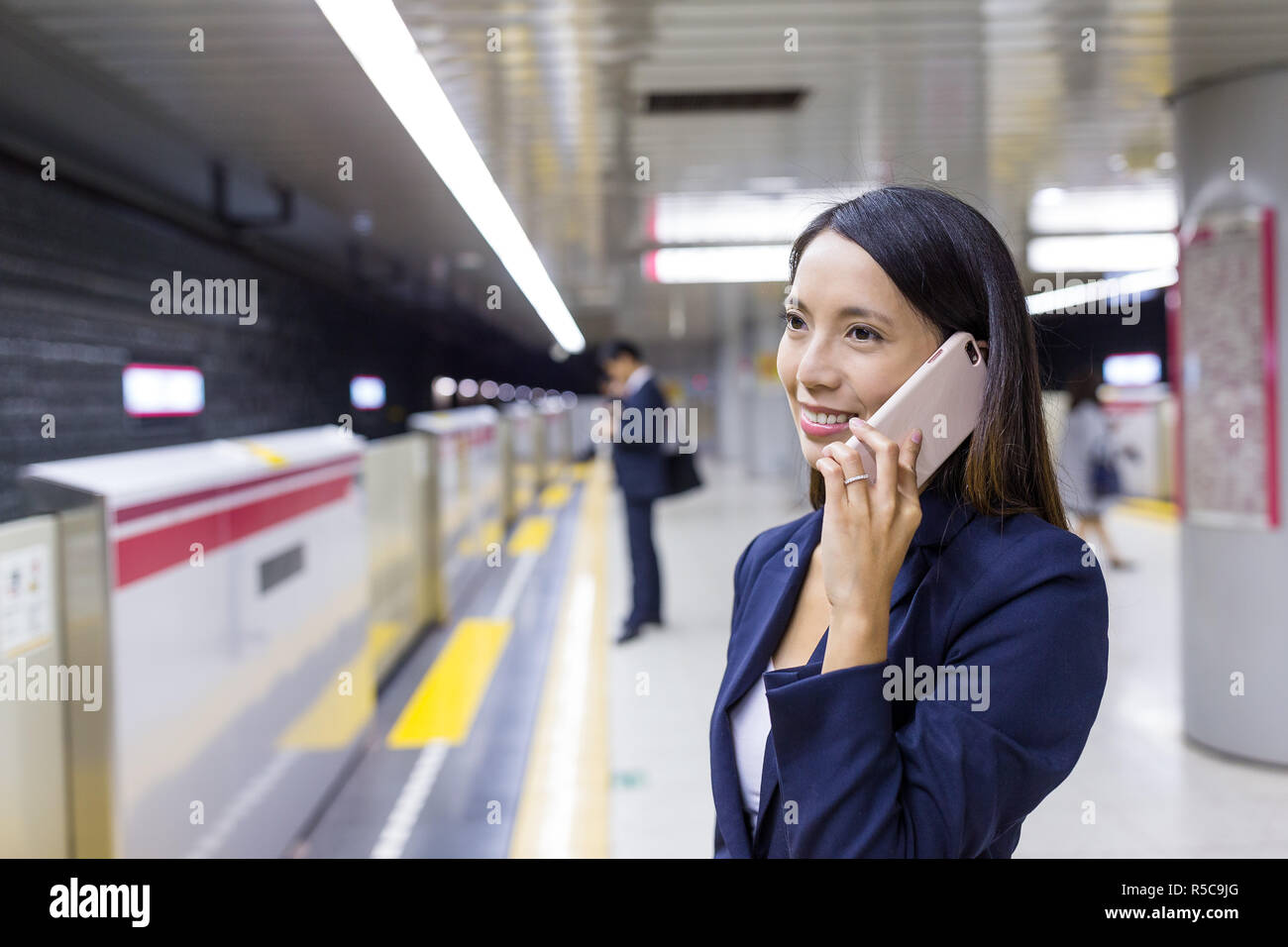 Businesswoman talk to cellphone in train station Stock Photo
