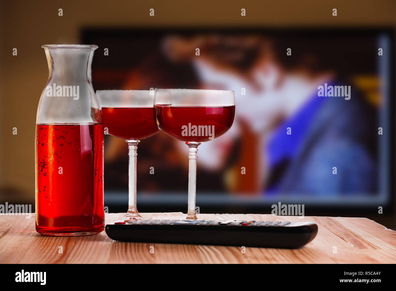 Two glass and carafe of wine with TV remote on light natural wooden table. Concept of romantic movie watching. - Stock Image