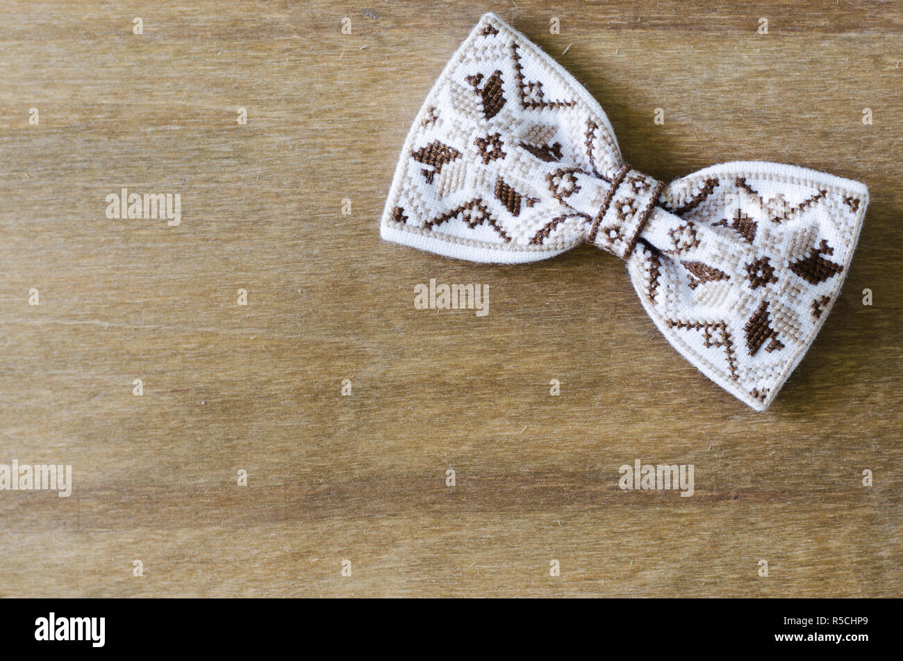 Embroidered Bow Tie on Wooden Brown Background. Father's day Concept. Rustic Style - Stock Image