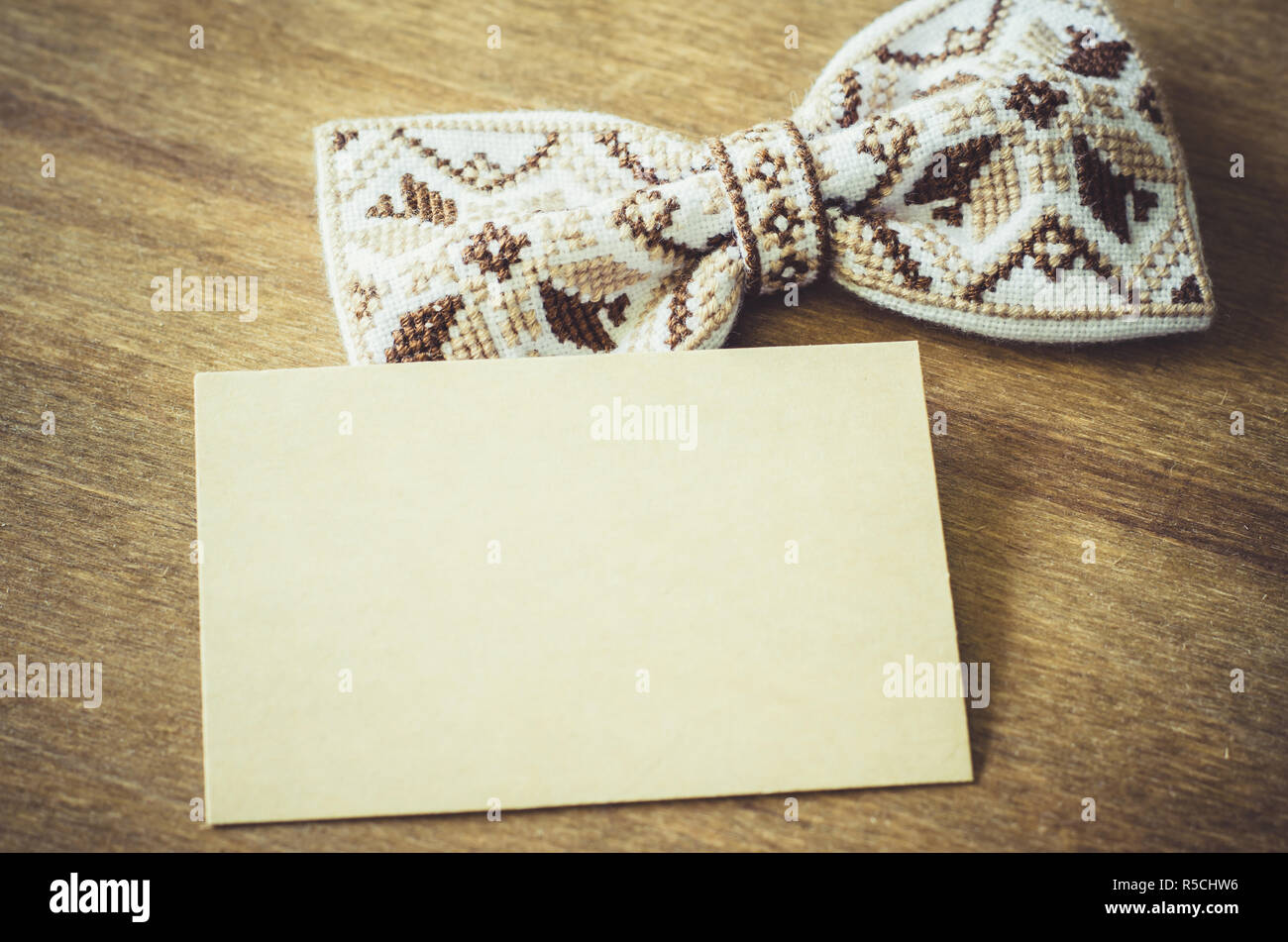 Embroidered Bow Tie and Empty Card on Wooden Brown Background. Father's day Concept. Rustic Style - Stock Image