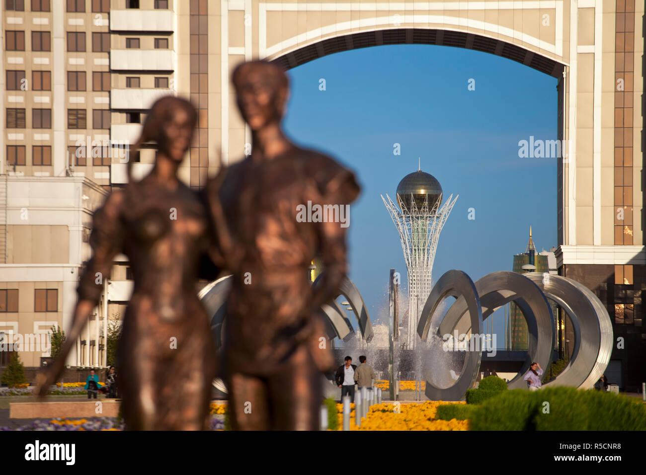 Kazakhstan, Astana, Statue infront of KazMunaiGas building home to the Oil and Gas Ministry, with Bayterek Tower in background Stock Photo